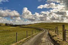 Une ruelle anglaise de pays menant par des terres cultivables Photos stock