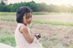 Une séance et elle mignonnes de fille jouant un chat sur planter le complot Photographie stock libre de droits