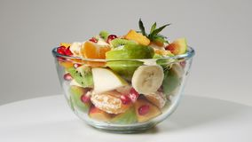 Une salade de fruits avec la mandarine, les oranges, le kiwi, les graines de grenade, les figues, la banane et les pêches banque de vidéos