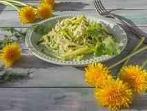 Une salade simple de vegan de katusta frais et concombres avec les herbes ?pic?es d'un plat rond de laitue, sur la table de conse photographie stock
