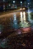 Une scène pluvieuse de rue de nuit conduisant par la ville photo libre de droits