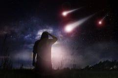 Une science-fiction éditent d'un homme que la position dans un domaine comme météorites expédient vers la terre la nuit avec les  images stock