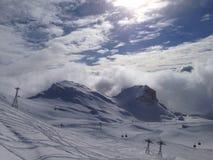 Une scène de ski de montagne sous un ciel bleu lumineux avec des nuages Photographie stock libre de droits