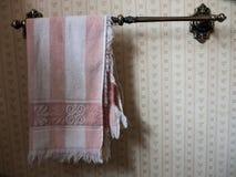 Une serviette de main rose et blanche pendant d'une barre Images libres de droits