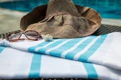 Une serviette turque, des lunettes de soleil et un chapeau de paille blancs et bleus sur le canapé de rotin avec une piscine bleu Photographie stock