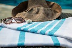 Une serviette turque, des lunettes de soleil et un chapeau de paille blancs et bleus sur le canapé de rotin avec une piscine bleu Photos libres de droits