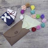 Une serviette vert clair colle hors de l'enveloppe de métier Décoré dans la forme du coeur avec les roses multicolores image plat Images stock
