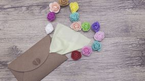 Une serviette vert clair colle hors de l'enveloppe de métier Décoré dans la forme du coeur avec les roses multicolores image plat Photos libres de droits