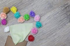 Une serviette vert clair colle hors de l'enveloppe de métier Décoré dans la forme du coeur avec les roses multicolores image plat Images libres de droits