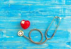 Une seule boule rouge simple d'exercice de main de forme d'amour de coeur avec le backgro en bois bleu de stéthoscope du ` s de m Photos stock