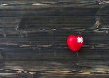 Une seule boule rouge simple d'exercice de main de forme d'amour de coeur avec le ` s de médecin de médecin de DM de bandage Photographie stock