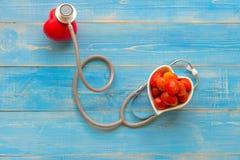 Une seule boule rouge simple d'exercice de main de forme d'amour de coeur avec le stéthoscope du ` s de médecin de médecin de DM  Photo stock