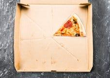 Une seule pièce de pizza dans la vue supérieure de boîte à pizza de carton de la boîte vide avec l'espace de copie sur le béton f image stock
