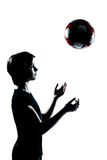 Une silhouette d'adolescent jetant le football en l'air du football Photo stock
