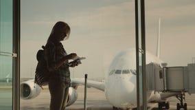 Une silhouette d'une femme avec des documents d'embarquement à disposition, attendant l'atterrissage sur son vol Supports à la fe banque de vidéos