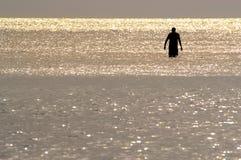 Une silhouette d'un homme pataugeant dans l'océan photo stock