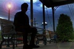 Une silhouette d'un homme s'asseyant sur un banc photographie stock libre de droits