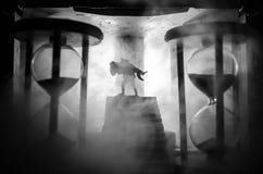 une silhouette d'un homme se tenant dessus sur la femme Concept de sauveur de délivrance Évasion du feu ou du danger Sablier, le  Images stock