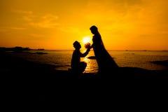 Une silhouette d'un jeune homme, vers le bas sur un genou et tenir un bouquet, proposant à son amie vous m'épouserez des images Image libre de droits