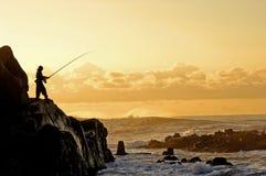 Une silhouette d'un pêcheur Image stock