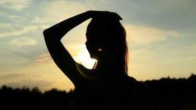 Une silhouette d'une femme sur un coucher du soleil la touchant banque de vidéos