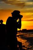 Une silhouette d'une fille qui cassent un coucher du soleil Image libre de droits