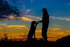 Une silhouette d'une jeune femme et de son chien de chien Image libre de droits