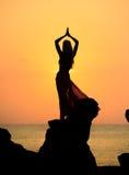 Une silhouette d'une jeune fille sur la roche au coucher du soleil 4 Photographie stock libre de droits