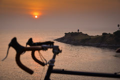 Une silhouette de bicyclette sur un coucher du soleil Paysage d'ÉTÉ Image stock