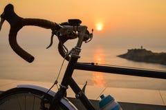 Une silhouette de bicyclette sur un coucher du soleil Paysage d'ÉTÉ Images stock