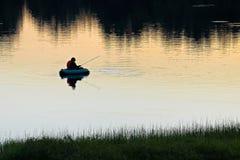 Une silhouette de la pêche de mouche de l'homme une soirée tranquille d'été Image libre de droits