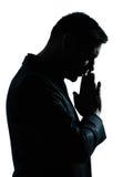 Une silhouette de prière pensante d'homme d'affaires Images stock