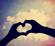 une silhouette des mains sous forme de coeur au-dessus d'un fond Photographie stock libre de droits