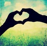 une silhouette des mains sous forme de coeur au-dessus d'un fond Photos libres de droits