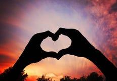 une silhouette des mains sous forme de coeur au-dessus d'un fond a modifié la tonalité avec un rétro effet de filtre d'instagram  Photographie stock