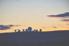 Une silhouette des satellites quand le soleil a placé dans le côté de pays Image stock