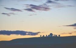 Une silhouette des satellites quand le soleil a placé dans le côté de pays Photographie stock libre de droits