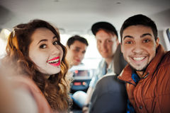 Une société de quatre amis fait le selfie à l'intérieur de la voiture Image libre de droits