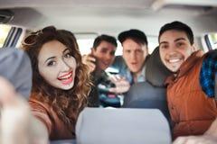 Une société de quatre amis fait le selfie à l'intérieur de la voiture Images stock