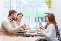 Une société des personnes ont l'amusement au café, mangeant de la nourriture et buvant du champagne Photo libre de droits
