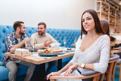 Une société des personnes passent le temps dans un café, la fille s'assied et examine pensivement la distance Image stock