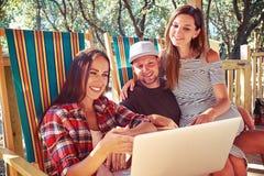 Une société gaie des personnes regardant un togethe se reposant d'ordinateur portable Photo libre de droits