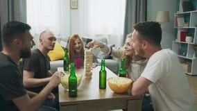 Une soci?t? des amis joue une tour en bois dans un salon confortable clips vidéos