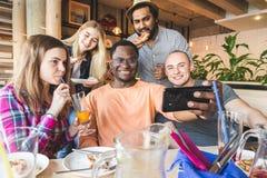 Une soci?t? des jeunes multiculturels dans un caf? mangeant de la pizza, cocktails potables, ayant l'amusement photo libre de droits