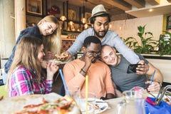 Une soci?t? des jeunes multiculturels dans un caf? mangeant de la pizza, cocktails potables, ayant l'amusement image stock