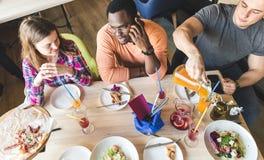 Une soci?t? des jeunes multiculturels dans un caf? mangeant de la pizza, cocktails potables, ayant l'amusement image libre de droits