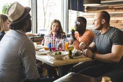 Une soci?t? des jeunes multiculturels dans un caf? mangeant de la pizza, cocktails potables, ayant l'amusement photo stock