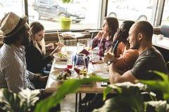 Une soci?t? des jeunes multiculturels dans un caf? mangeant de la pizza, cocktails potables, ayant l'amusement images stock