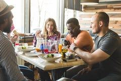 Une soci?t? des jeunes multiculturels dans un caf? mangeant de la pizza, cocktails potables, ayant l'amusement images libres de droits