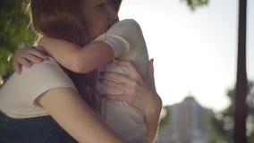 Une soeur plus âgée étreignant avec le jeune frère dehors Mouvement lent banque de vidéos
